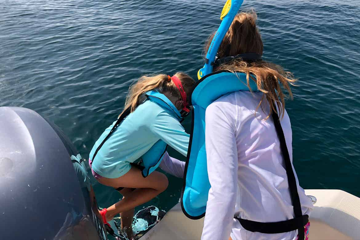 Featured Contributor, Chris Johnston's two daughters, Kyler (right) and Kyndall (left), wear multi-colored snorkel gear while stepping into the ocean.