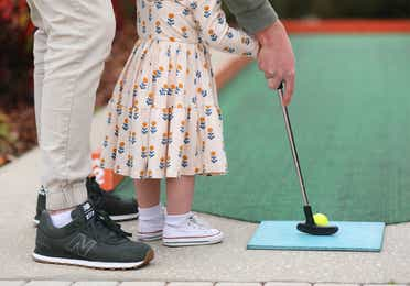 A toddler and adult playing mini golf
