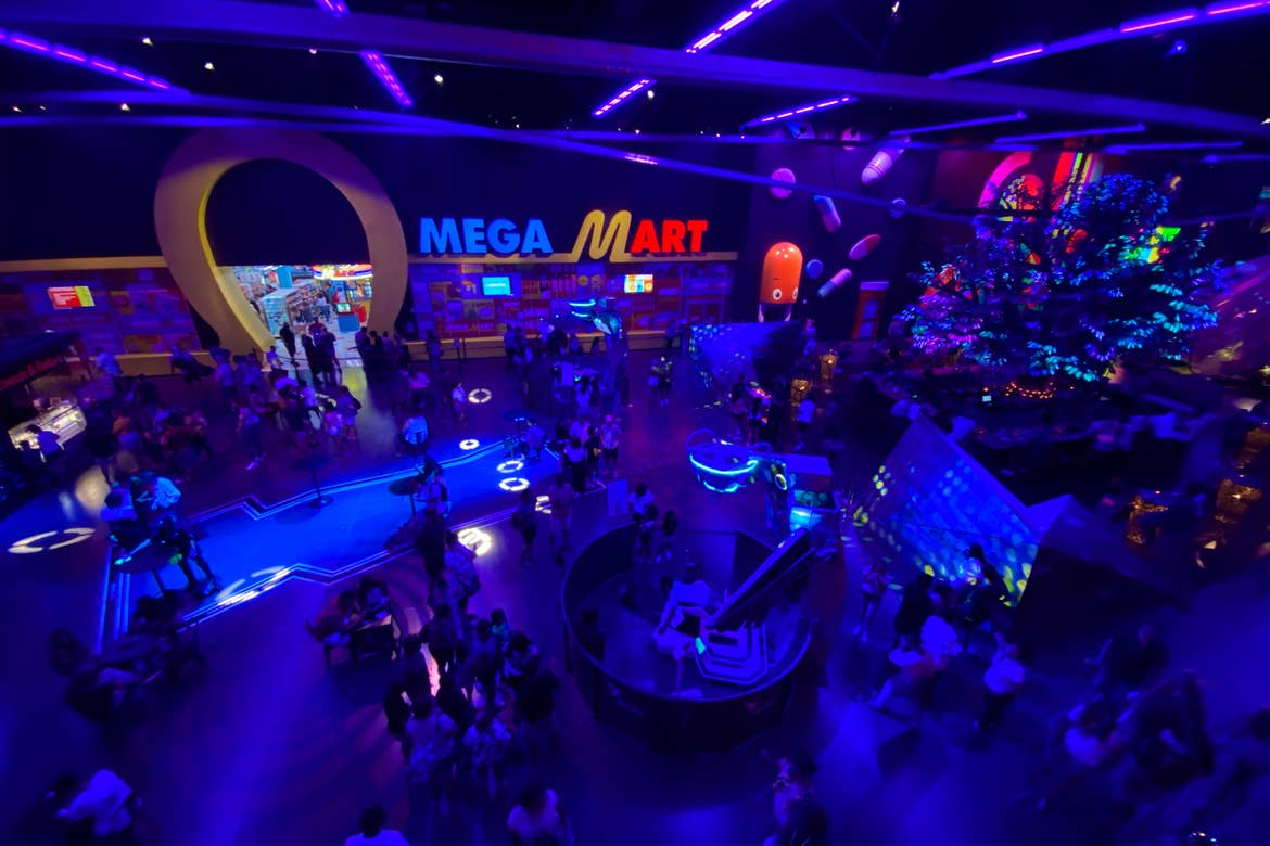An interior space with blue lighting and an illuminated marquee that reads, 'Mega Mart' in yellow and red neon contains numerous guests.