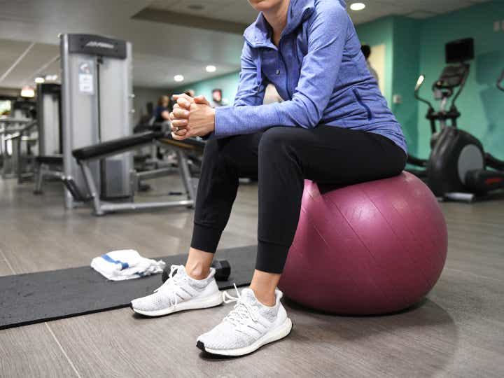 Woman sitting on yoga ball in a fitness center at Lake Geneva Resort in Wisconsin.