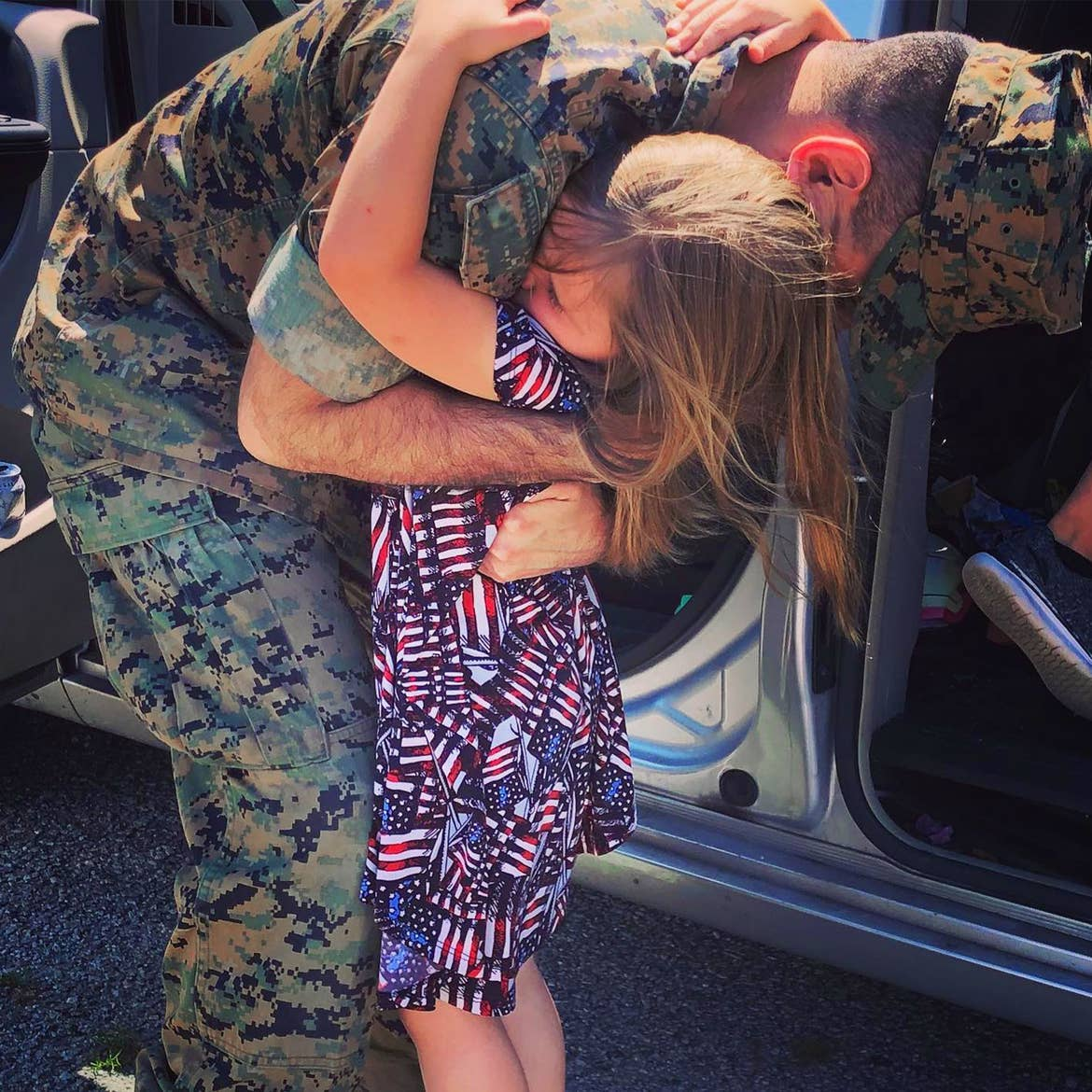 Sara Perezes youngest daughter (right) is held by her dad in his uniform as he leaves for deployment.