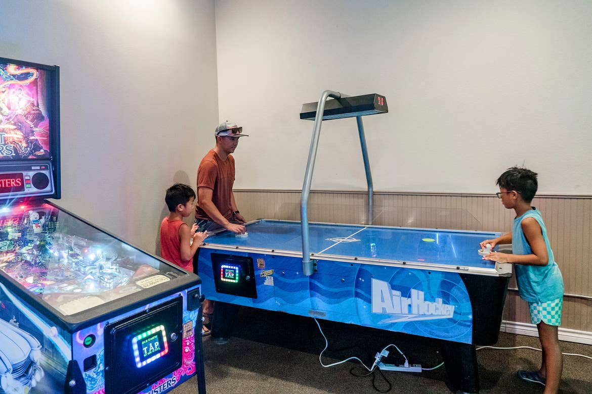 An Asian man (back-left) and two young Asian boys (left and right) play at a blue air hockey table near an illuminated pinball machine at our Villages resort in Flint, Texas.