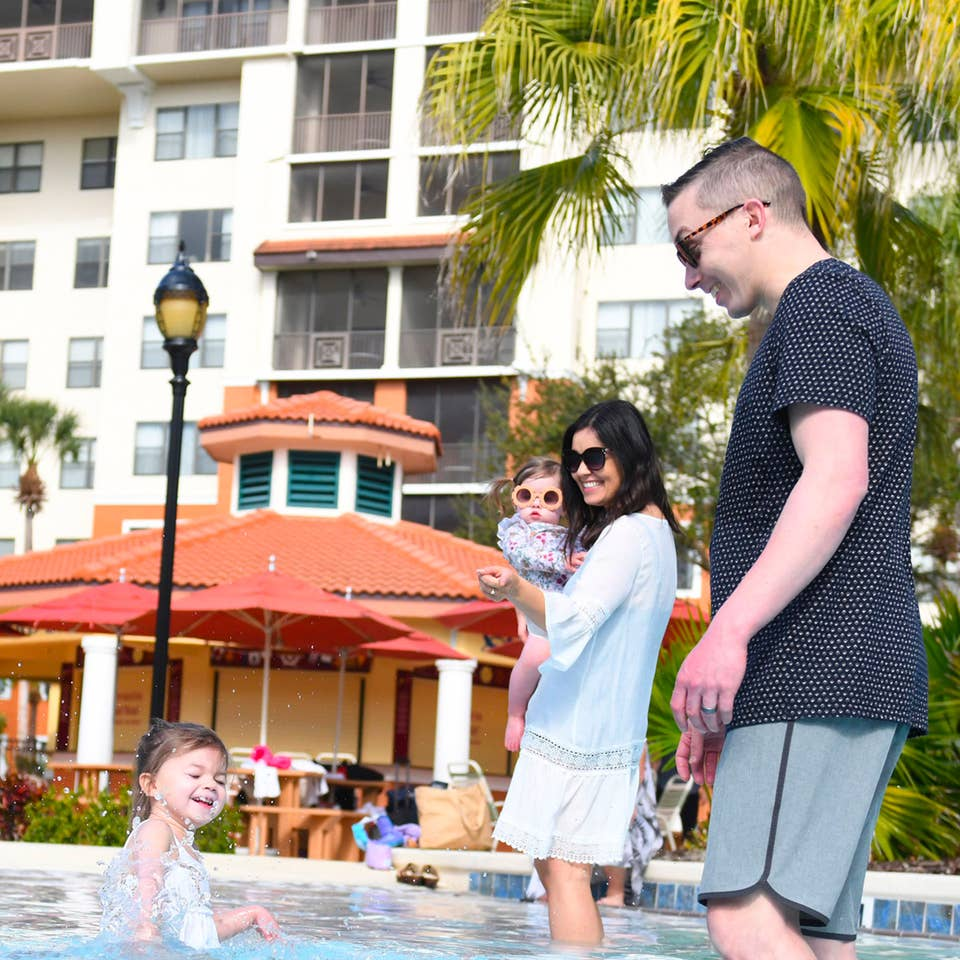 A couple and their two children wading in the pool at Orange Lake Resort in Orlando, FL