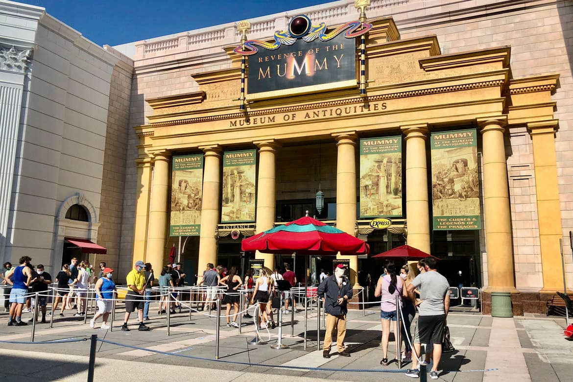 'Revenge of the Mummy' attraction entrance facade with guests in socially distant queue.