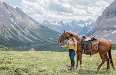 Featured Contributor, Ashlyn George, stands with a horse in front of the Canadian mountain range.