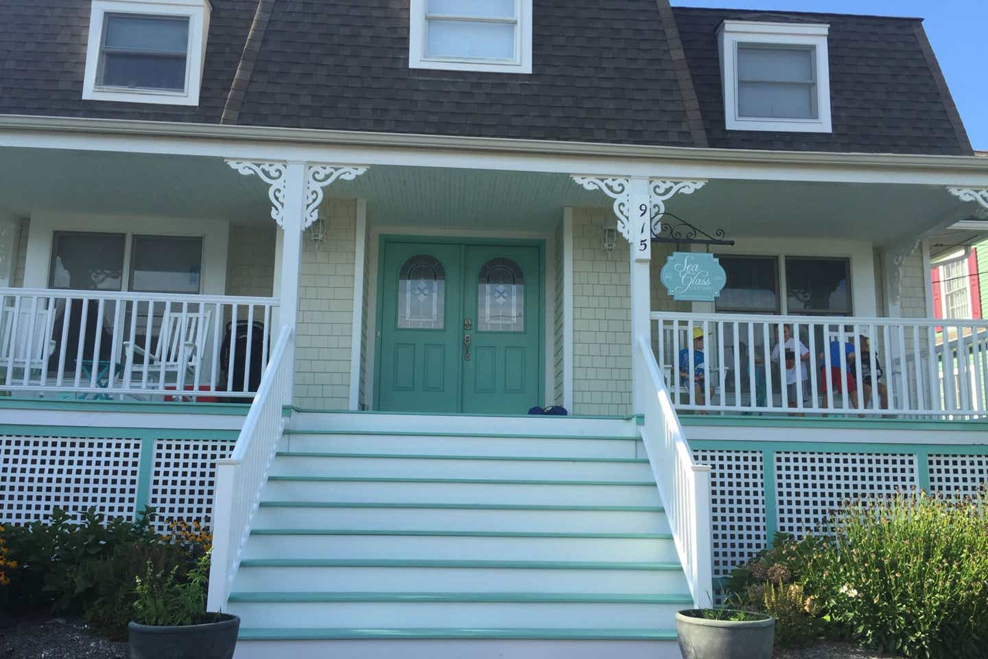 Exterior shot of the Sea Glass Cottage at Cape May with a wrap-around white porch and aqua siding and doors.