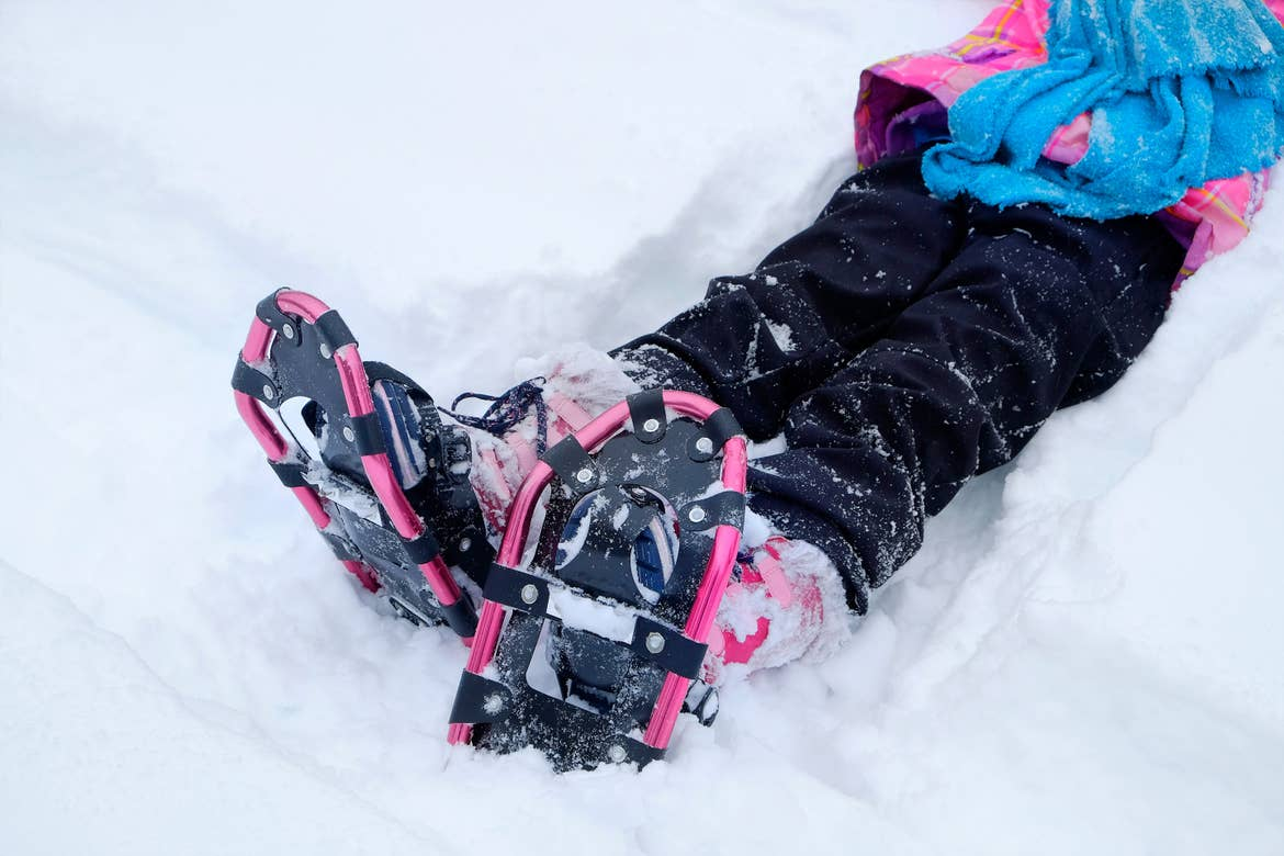 A girl sits in the snow wearing a blue and pink jacket, black snow pants and a pair of pink and black snowshoes.