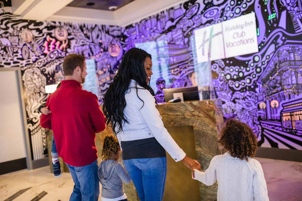Featured Contributor, Sally Butan (middle-right) of @butanclan walks towards a check-in desk near our purple animated mural in the lobby at our resort in New Orleans, Louisiana.