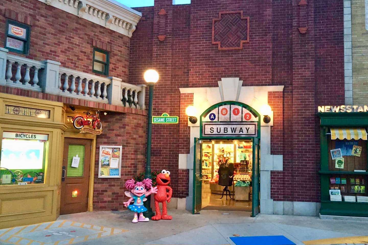 Exterior shot of Sesame Street Land where Elmo and Abby Cadabby stand under the streetlamp in front of the subway.