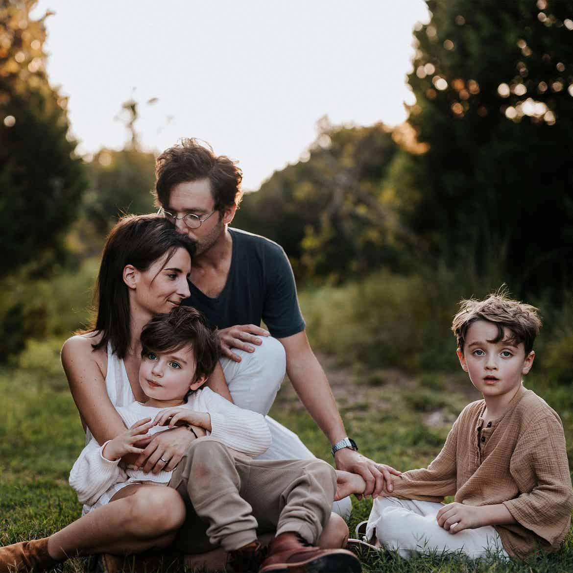 Featured Contributor, Eileen Lamb (middle-left), her husband (top-left) and sons, Jude (front-left) and Charlie (right) sit outdoors on the grass at dusk.