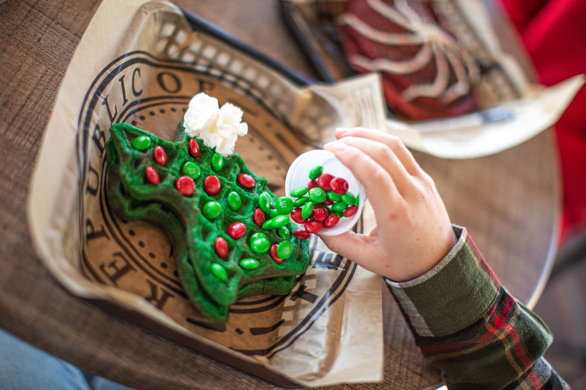 A guest enjoys a green, Texas-shaped waffle with whipped cream and red and green m&m's at our 'Jollydays' event at our Hill Country resort in Texas.