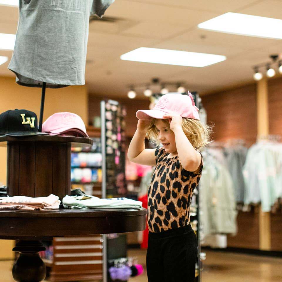 Young child trying on a Las Vegas hat in Marketplace at Desert Club Resort in Las Vegas, Nevada.