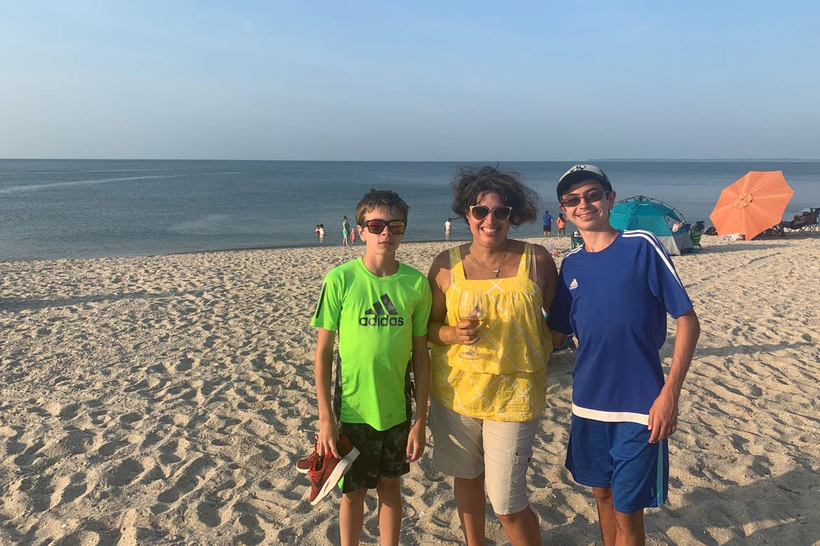 Author, Jennifer Probst (middle), and her sons (left and right) stand on the beach in front of the Cape May waterfront.