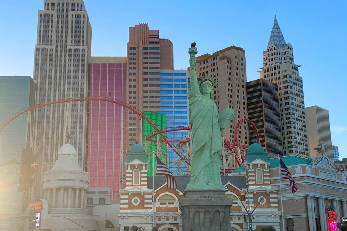 A scaled 'Statue of Liberty' and New York Skyline has red rollercoaster tracks intertwined in the air under a blue sky.