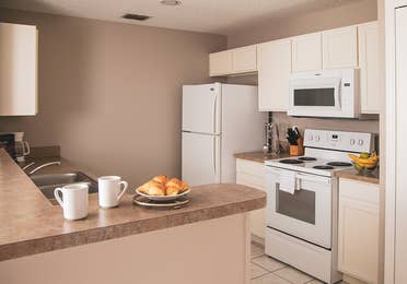 Full kitchen with fridge, stove and microwave in a two-bedroom villa at Orlando Breeze Resort in Florida.