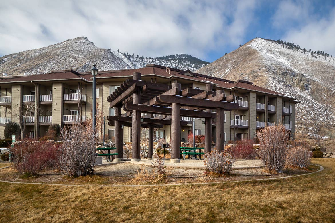 An exterior shot of David Walley's Resort with snow-capped mountains in the distance.