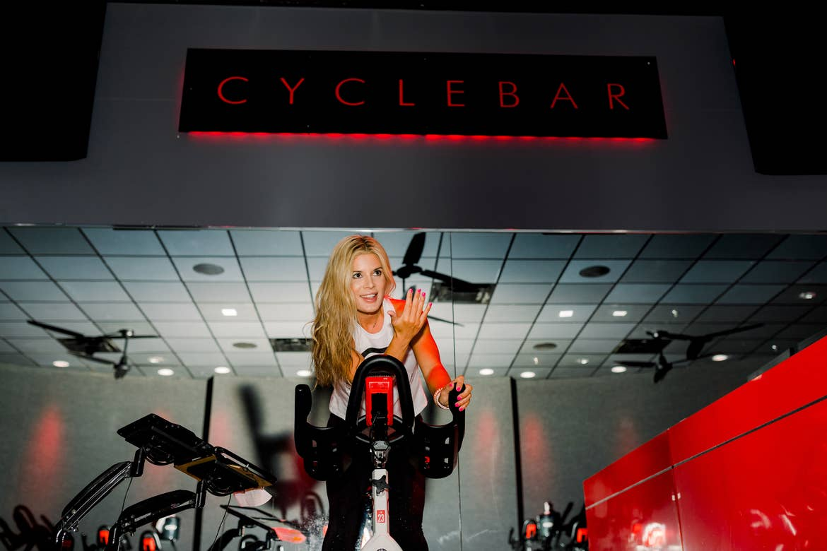 Co-author, Jessica, wears a white sports bra and black leggings while riding a cycle bike in a black room with red lights in the background.