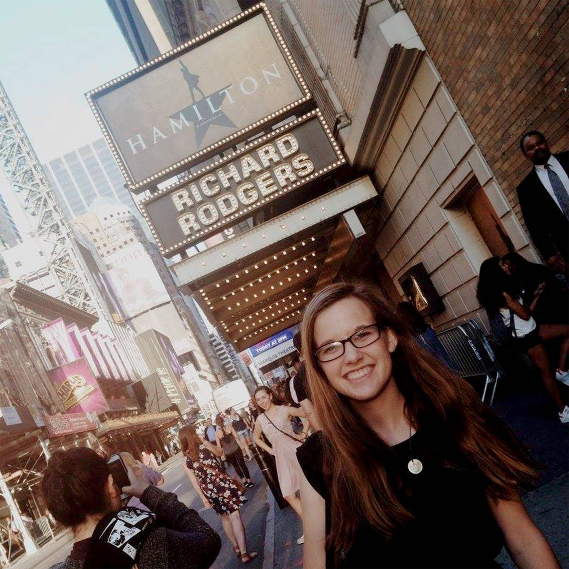 A caucasian woman with long ash-blonde hair wears a pair of black sunglasses and t-shirt under a marquee that reads, 'Hamilton, Richard Rodgers Theater' in New York City.
