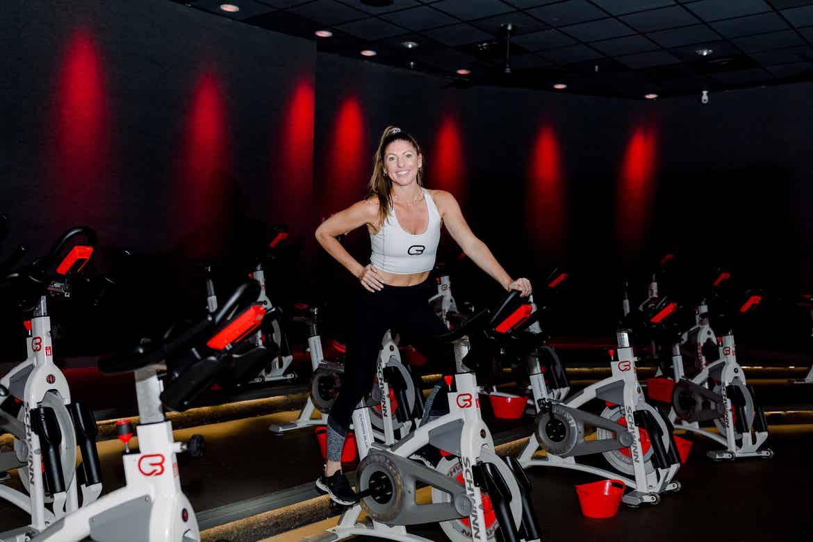 Co-author, Christine, wears a white sports bra and black leggings while riding a cycle bike in a black room with red lights in the background.
