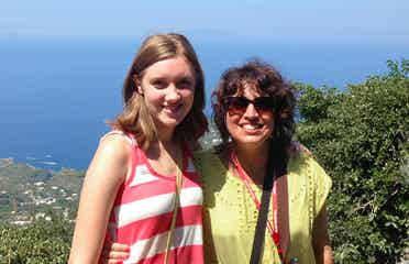 Featured Author, Jennifer Probst (right) stands with her niece (left) in front of a hill that overlooks the coastline of Italy.