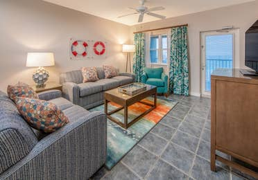Living room with two couches, an accent chair, flat screen TV, and coastal decor in a two-bedroom villa at Panama City Beach Resort
