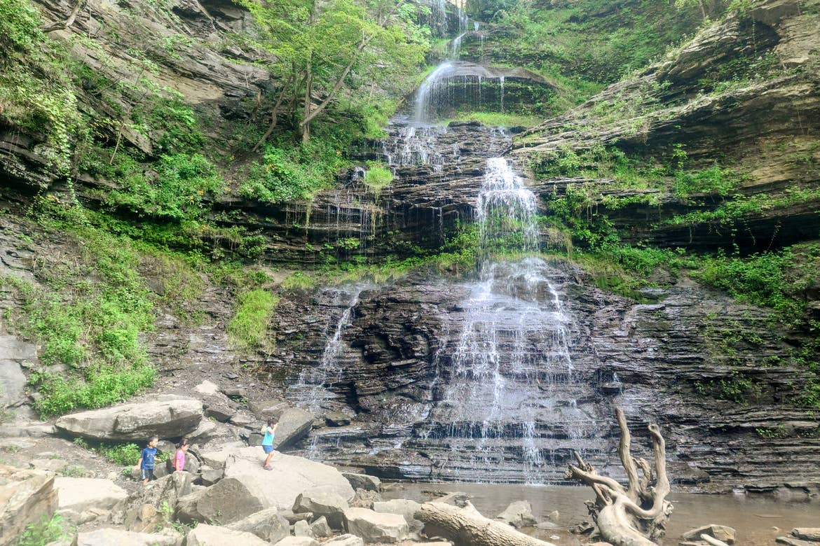 Three Asian Pacific Islander toddlers (left to right: Two girls and a boy) wear shorts and t-shirts while climbing rocks near a waterfall.