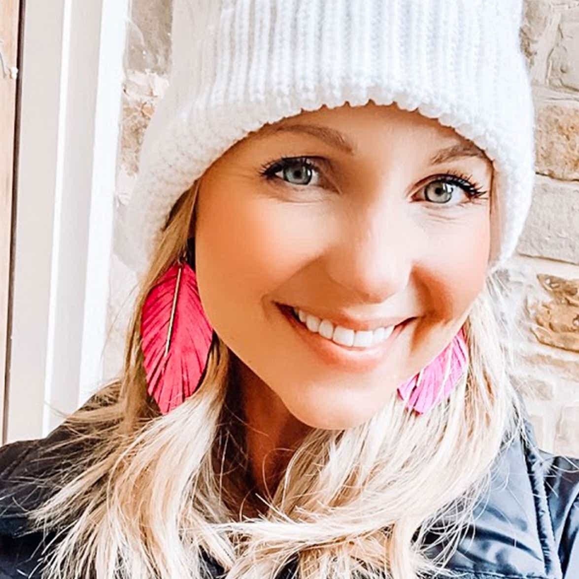 Amanda Nall selfie with pink feather earrings and a white knit cap
