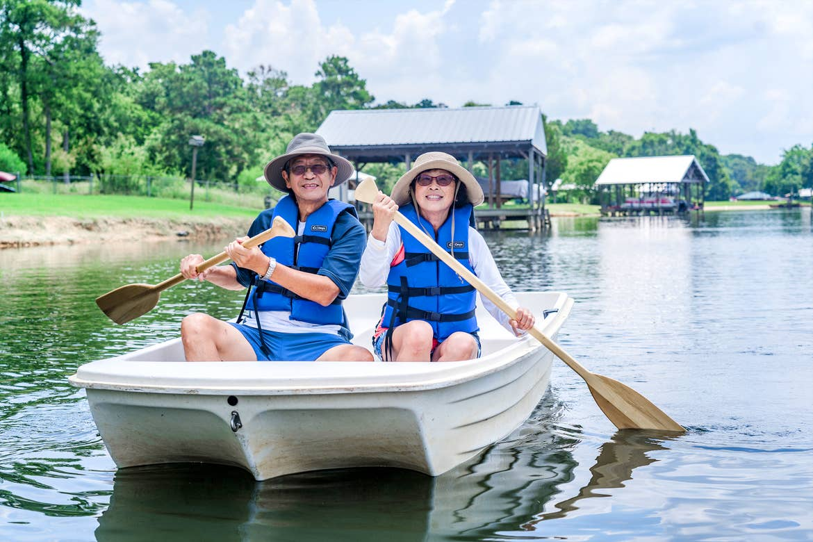 An older Asian male (left) and female (right) wear blue life vests, sunglasses and various hats while riding on a white rowboat in a lake.