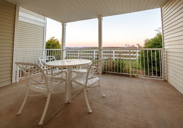Furnished balcony with table and four chairs in a Presidential two-bedroom villa at Ozark Mountain Resort in Kimberling City, Missouri