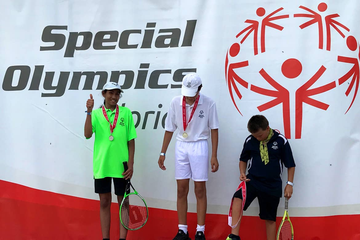 Special Olympic Athlete, Roan Luallen, wears a neon green t-shirt and black shorts while holding a tennis racket and wearing a medal along with two other competitors at the Special Olympics in 2019.