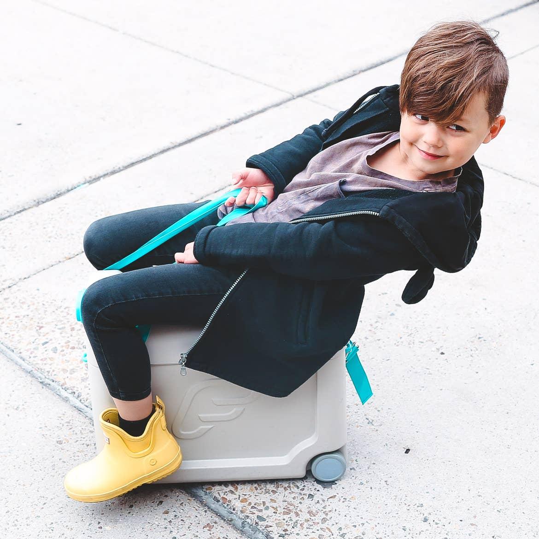 Mia's son sitting on suitcase