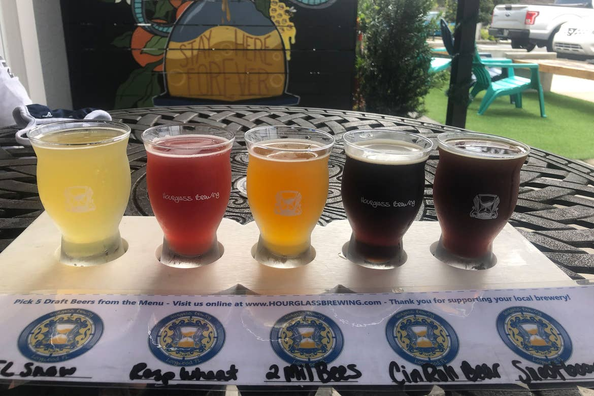 A beer flight with a label that reads abbreviations, '1. FL Snow 2. Raspberry Wheat 3. 2 Million Bees 4. Cinnamon Roll Bear 5. Snootboops from 'Hourglass Brewing.'