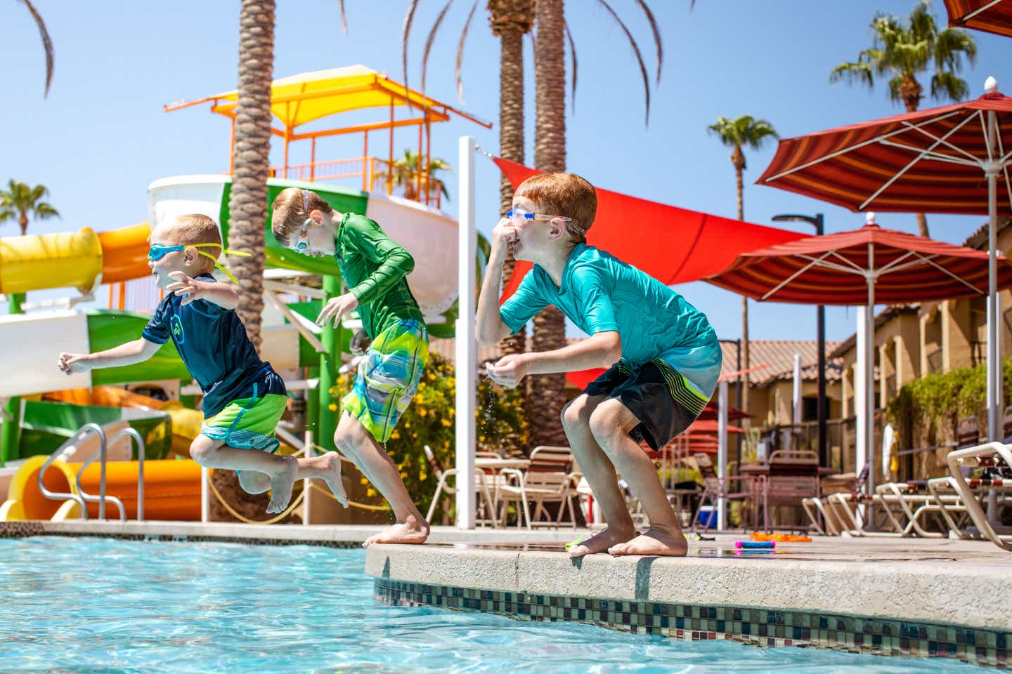 The Averett boys, wearing all their swimwear, jump into the pool near our water slides at our Scottsdale Resort.