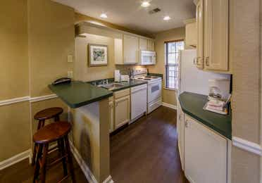 Full kitchen with bart-top and stools in a two bedroom villa at Oak n' Spruce Resort in South Lee, Massachusetts