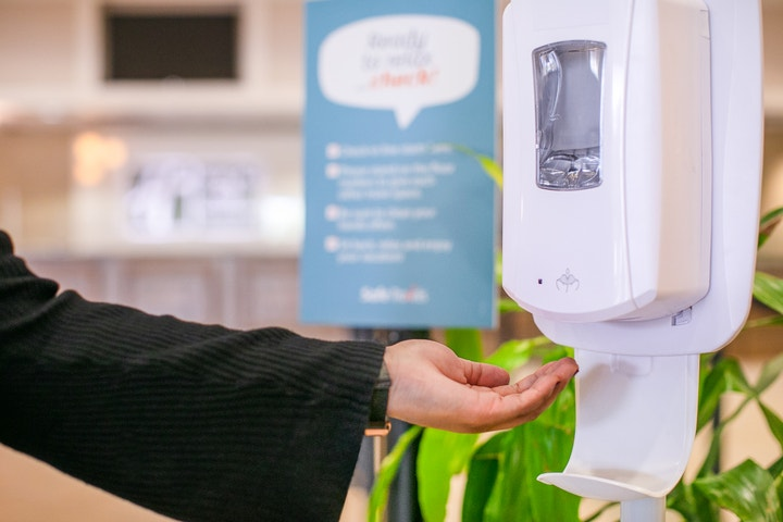 Hand reaching towards automatic hand sanitizer dispenser.