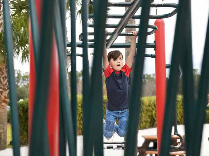 Child hanging from monkey bars at playground in Orange Lake Resort near Orlando, Florida.