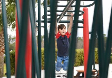 Child hanging from monkey bars at playground in Orange Lake Resort near Orlando, Florida.
