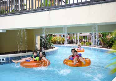 Family floating on inner tubes down lazy river at Orange Lake Resort near Orlando, Florida