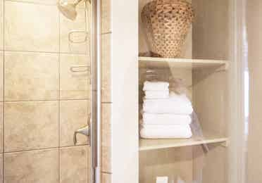 Closeup of walk-in shower and wall storage holding white folded towels in a Signature villa in River Island at Orange Lake Resort near Orlando, Florida