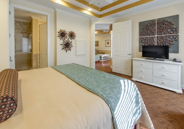 Bedroom with flat screen TV and attached bathroom in a presidential villa at Fox River Resort in Sheridan, Illinois
