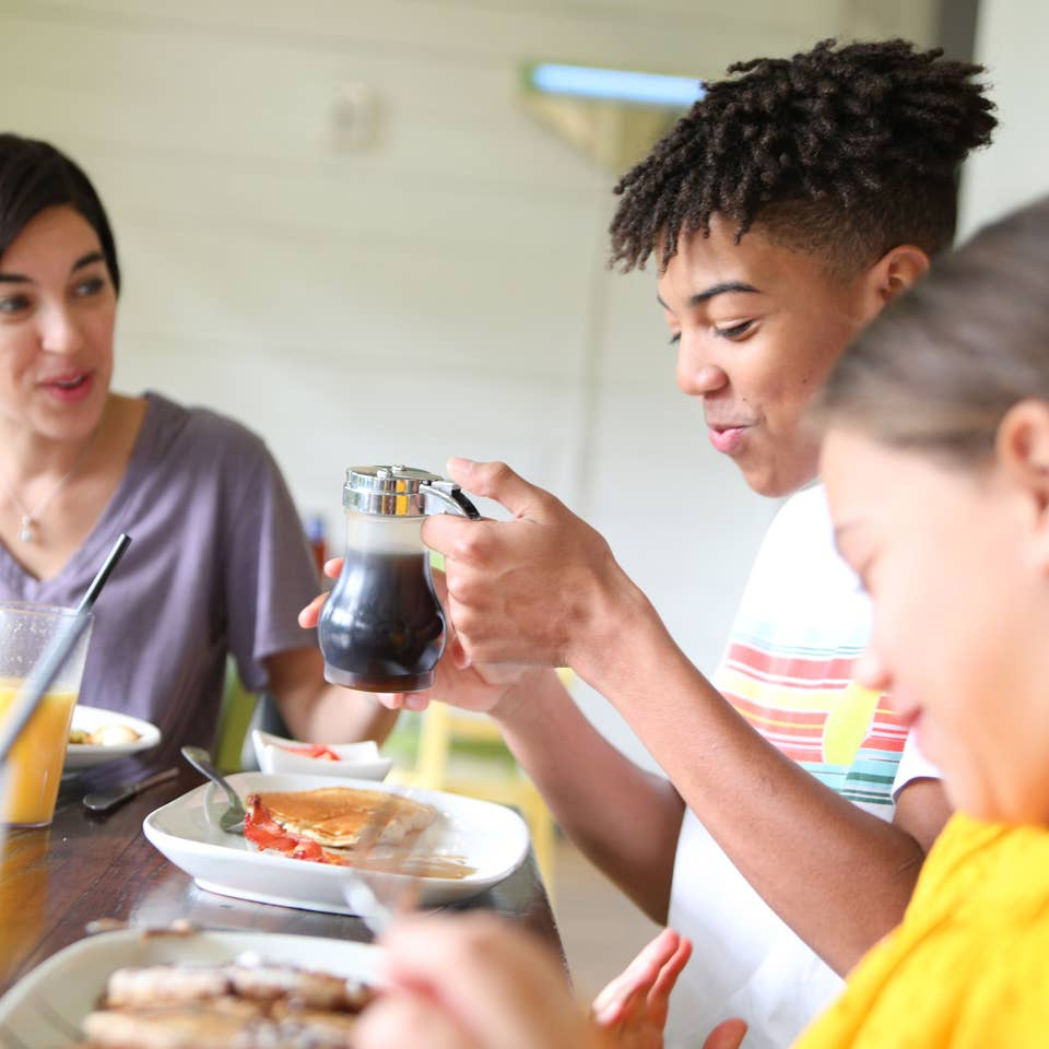 Mother and two children at breakfast table with pancakes