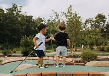 Two toddlers holding golf clubs at a mini golf course at Williamsburg Resort