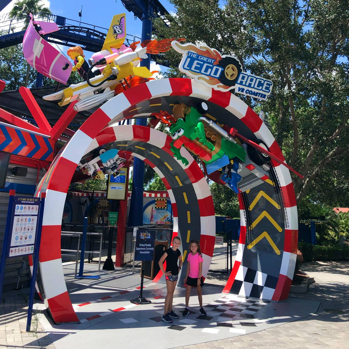 Two young girls stand under a entry arch made of LEGOS.