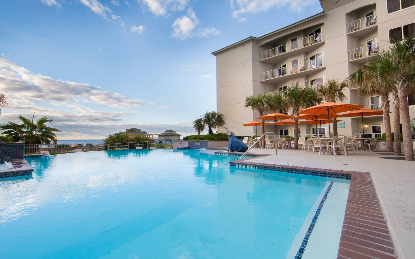 Outdoor pool surrounded by palm trees and umbrelles at Galveston Beach Resort