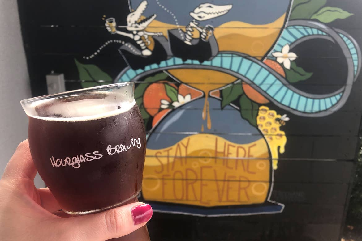 A hand holds a beer glass with the 'Hourglass Brewing' logo on it in front of a wall mural that reads, 'Stay Here Forever' at  'Hourglass Brewing.'