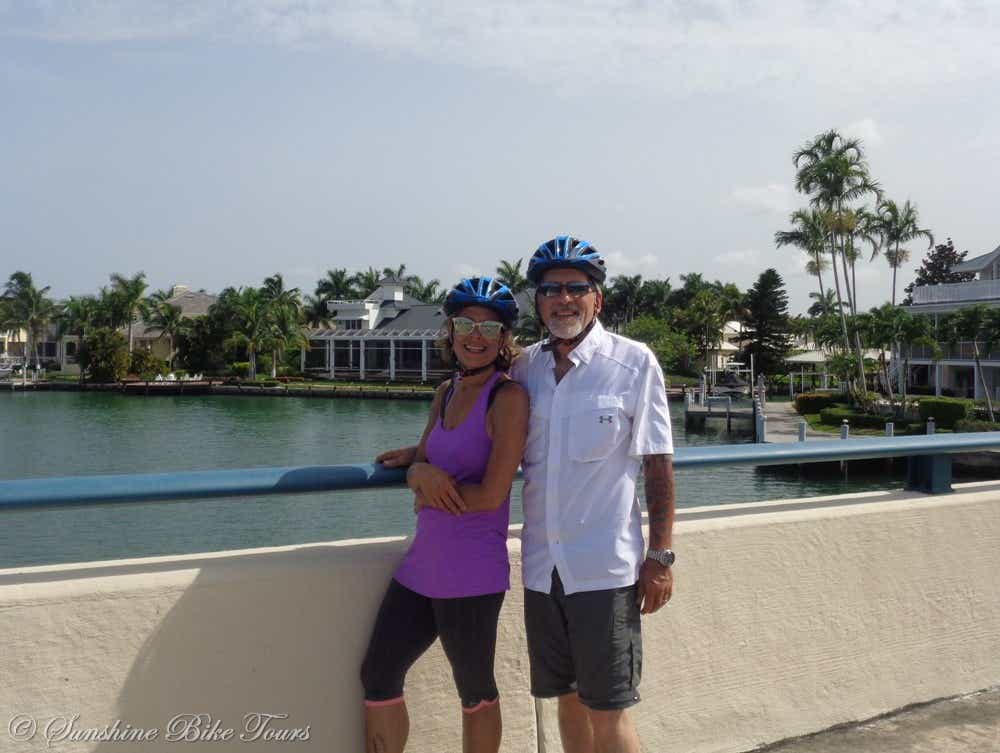 Denise and CJ with their helmets on posing in front of the canal on Marco Island