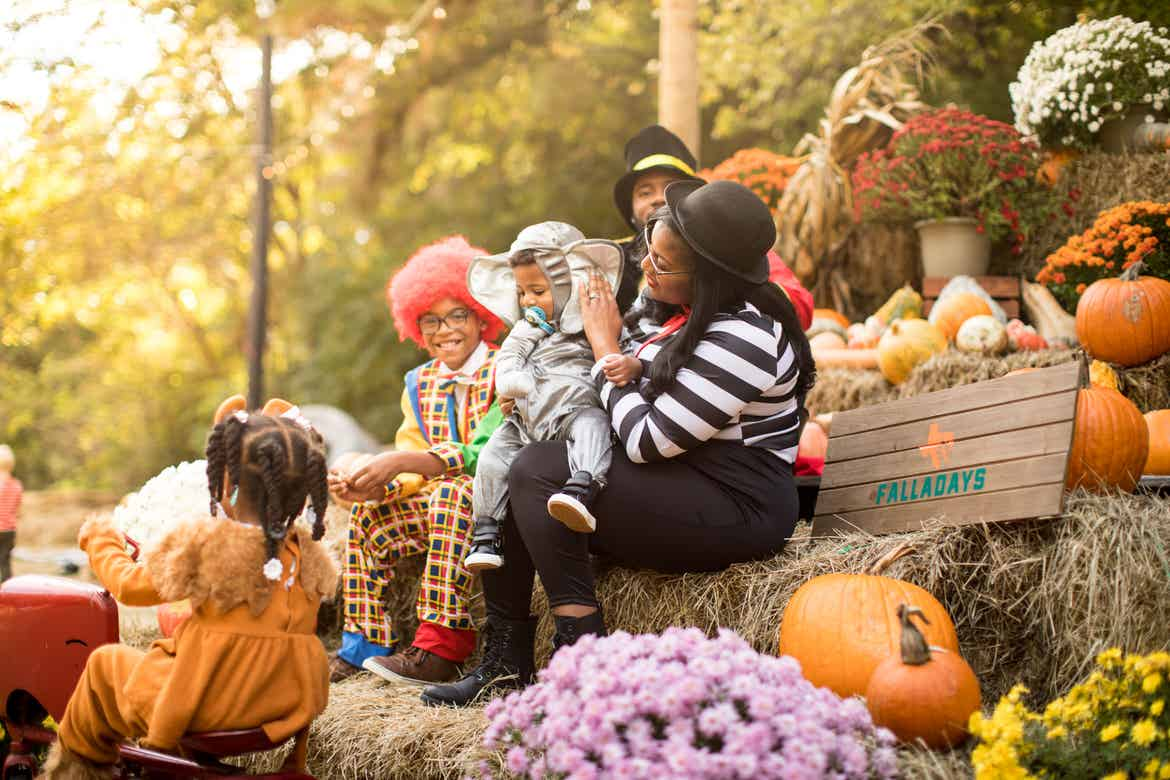 Tina and her children dressed in Halloween costumes sitting on the pumpkin display at Falladays at Villages Resort.