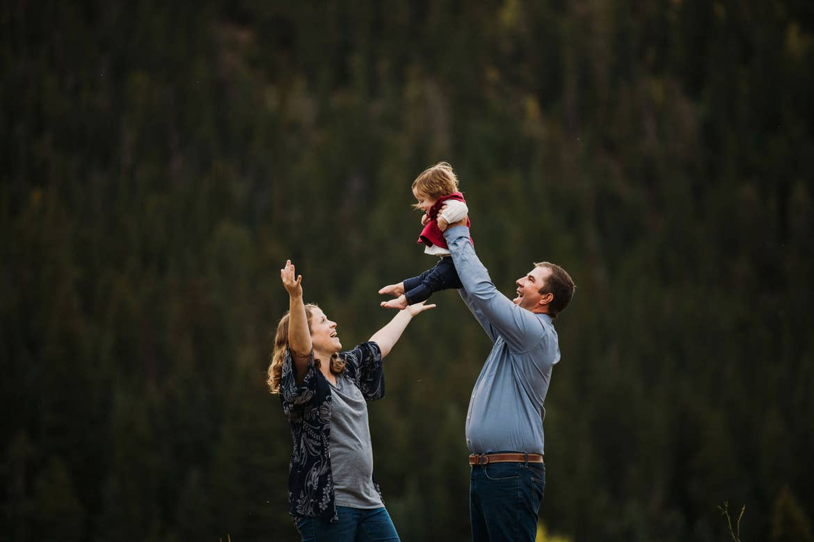 A mother (left) lifts her expressive arms as a father (right) holds up their child in front of a wooded area.