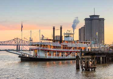 New Orleans Steamboat and bridge at sunset.