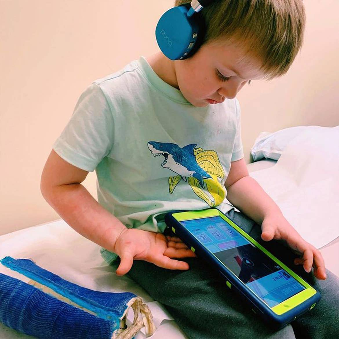 Featured Contributor, Alicia Trautwein's son holds an iPad while wearing headphones.